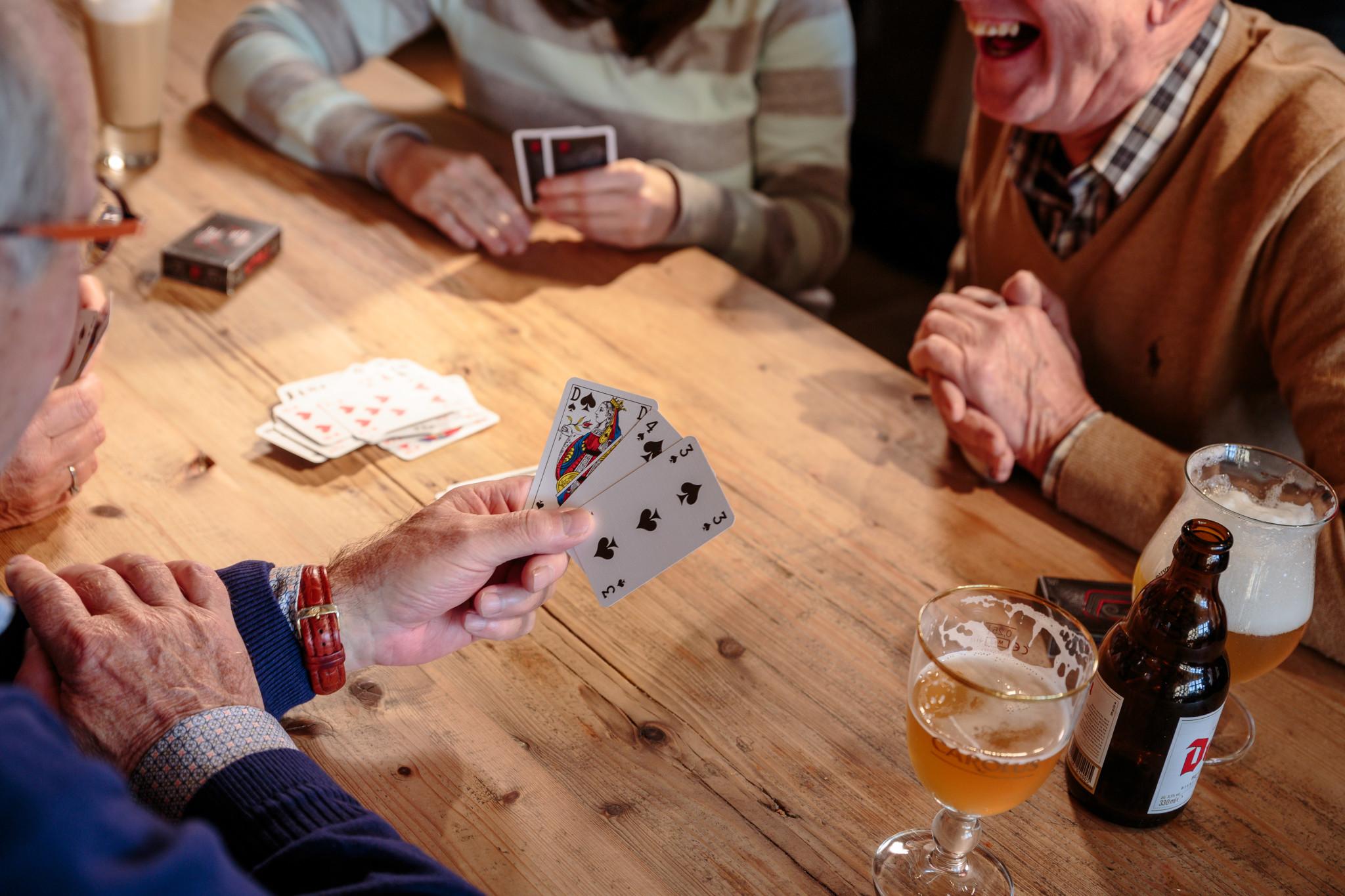 Leute spielen mit Jasskarten im Café